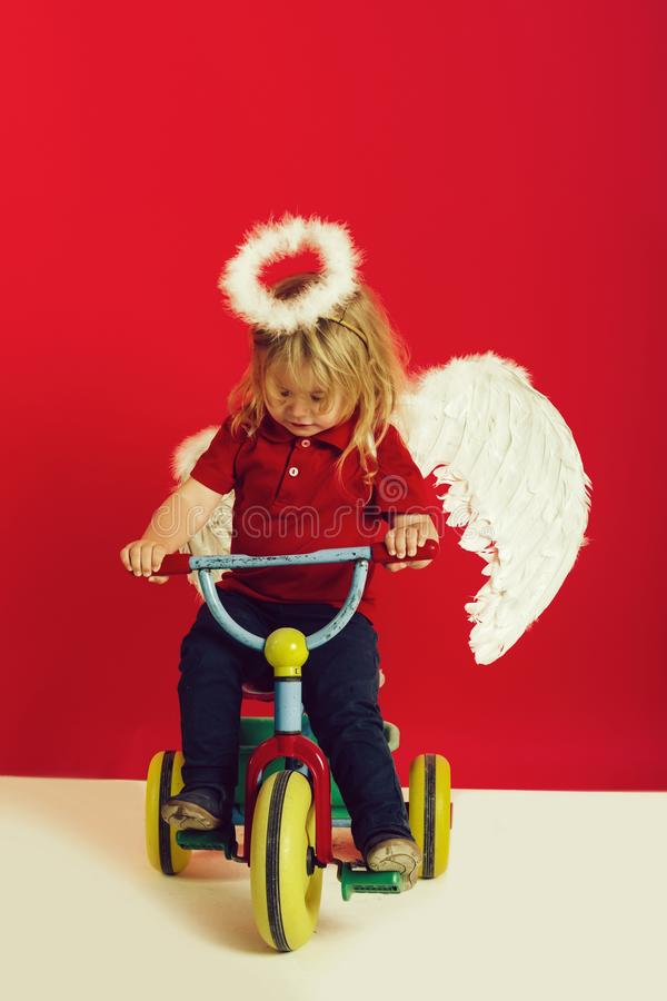 Angel boy for valentine greeting, beautiful cupid on bike. Beautiful cupid on bike with blonde hair and halo, angel boy on red background for valentine greeting stock images