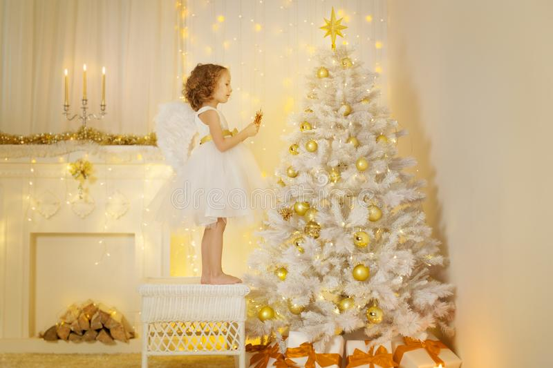 Angel Child Decorating Christmas Tree, Girl Hanging Decoration. Presents in Holiday Room with Fireplace stock image