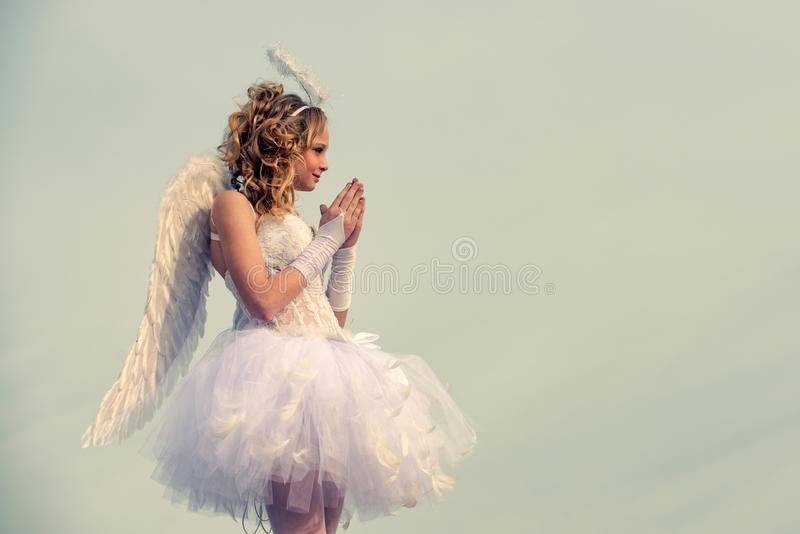 Angel child girl with curly blonde hair - Innocent girl concept. Teenager Cherub Cupid. Child with angelic character. Sweet angel girl. Pray. Angel wings baby royalty free stock photography