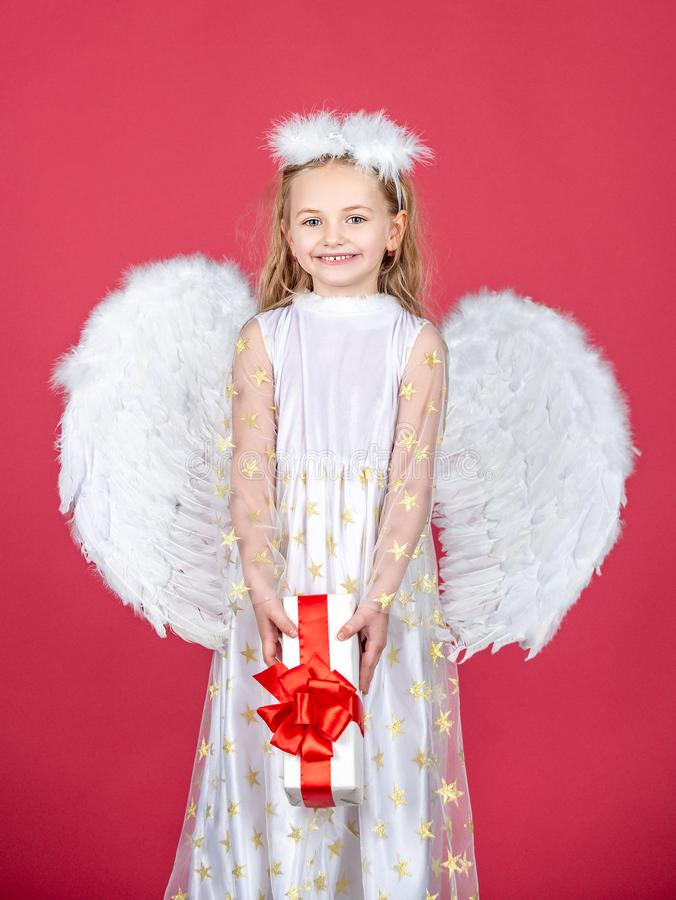 Angel child from heaven gives you gift. Cute toddler girl in white wings as Cupid. Angel kid with blonde curly hair stock photography