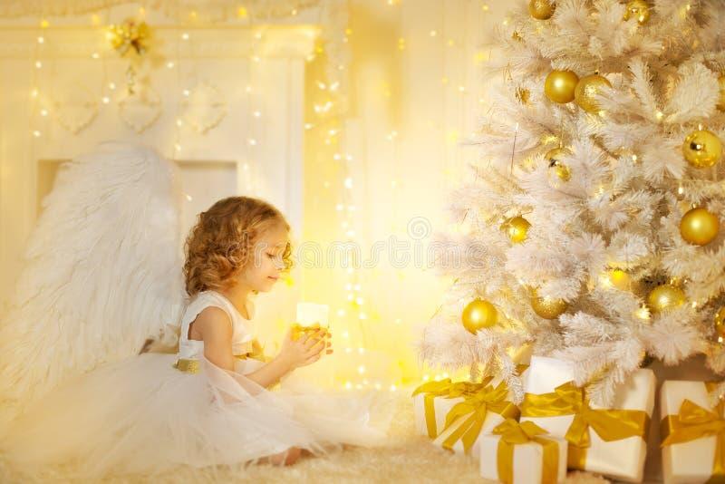 Angel Child och julgran med gåvagåvor, ungeflicka arkivfoton