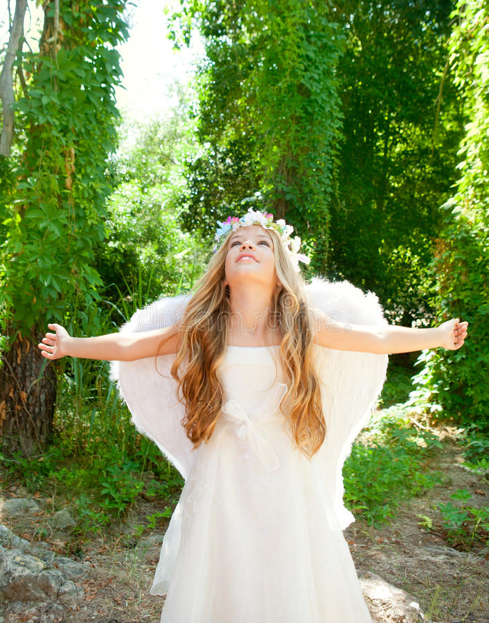 Angel children girl in forest white wings stock photo