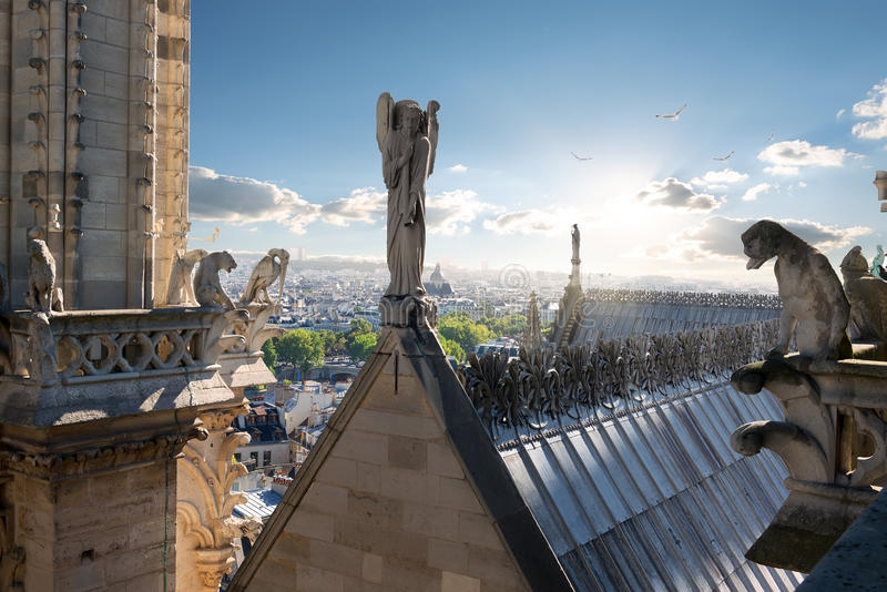 Angel and chimeras. Statues of Angel and Chimeras on the roof of Notre Dame de Paris, France royalty free stock photography