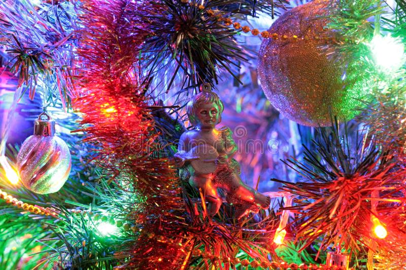 Angel, Christmas decoration and beautiful illumination. Yellow, green, red, and blue gerland illuminate this toy, creating the effect of a fairy tale of royalty free stock images