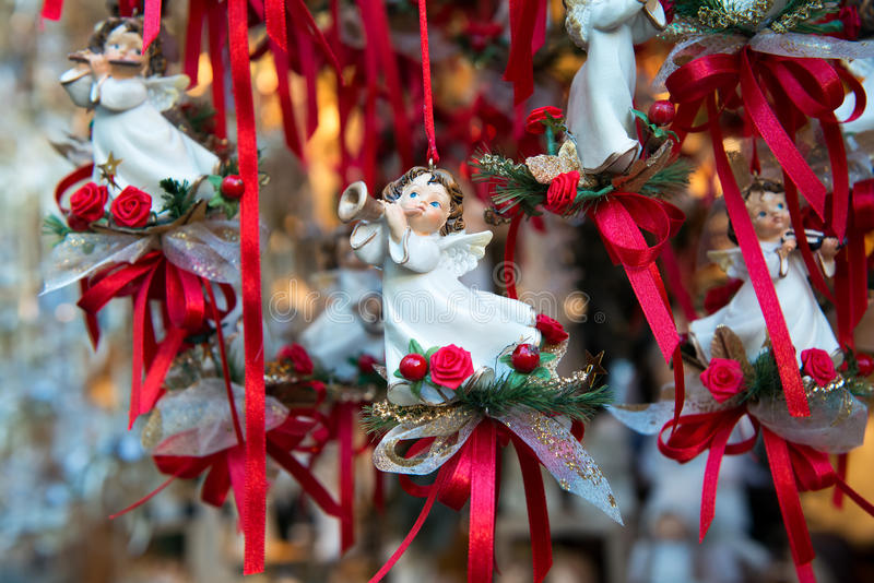 Angel Christmas ornaments at market. Angel ornaments blowing trumpets hanging on colorful red ribbons for sale at a seasonal Christmas market royalty free stock image