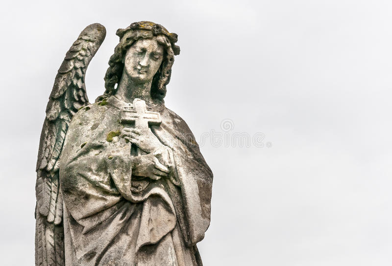 Angel with a cross. Public sculpture of angel in the cemetery royalty free stock photo