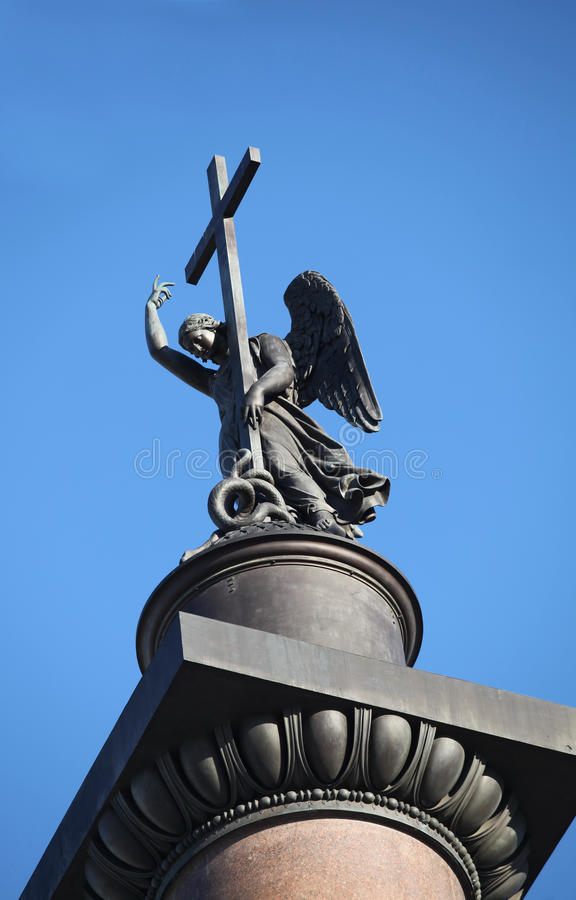 Angel with cross. Statue of winged angel with cross in blue sky royalty free stock photography