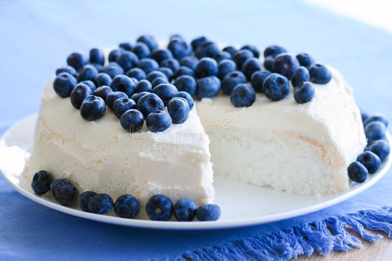 Angel food cake. Decorated with fresh blueberries and cream royalty free stock photography