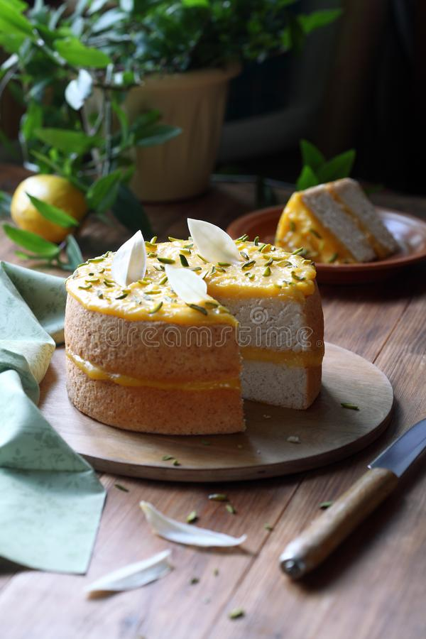 Angel Food Cake with Lemon Curd. Decorated with pistachios and white chocolate leaves, on wooden board, on wooden table royalty free stock photos