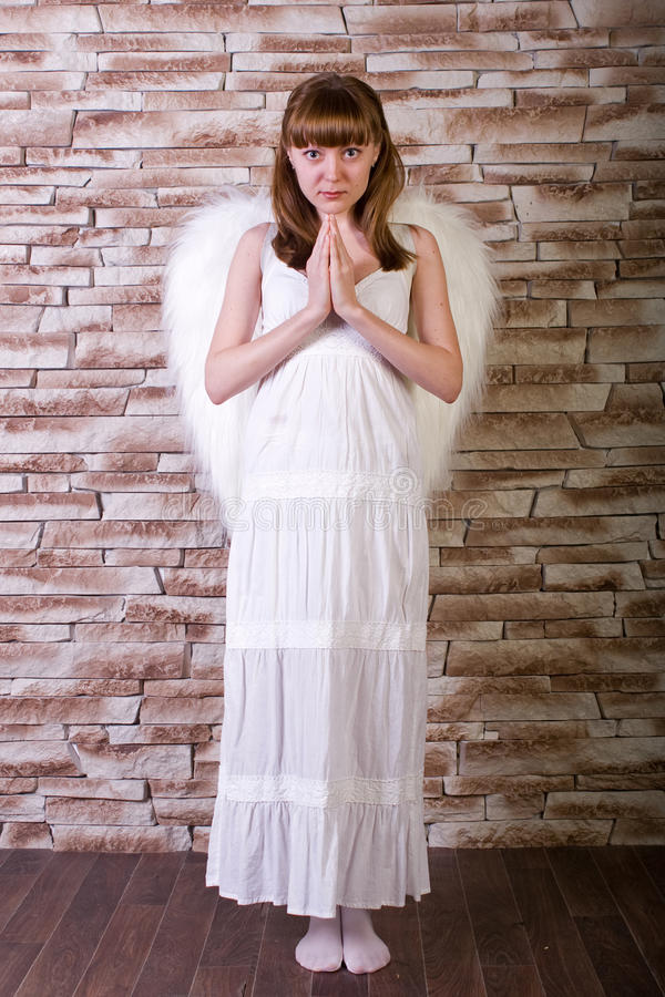 Angel girl. On brick wall background stock image