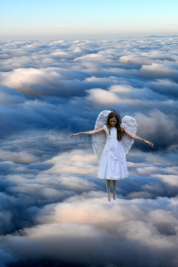Angel girl above the clouds royalty free stock photo