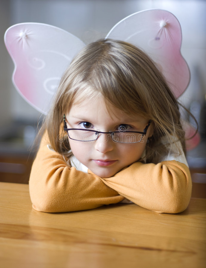 Angel girl with attitude. Portrait of a young girl, wearing angel wings and eyeglasses royalty free stock images