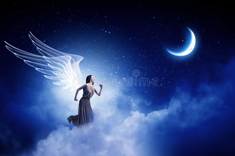 Angel girl in dress. Attractive woman running with angel wings behind back royalty free stock image
