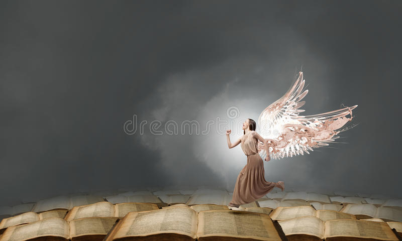 Angel girl in dress. Attractive woman running with angel wings behind back royalty free stock photography
