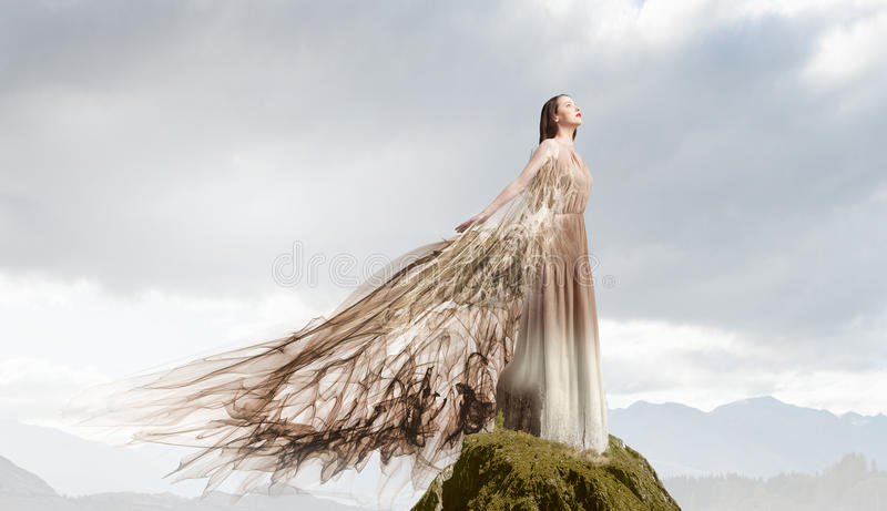 Angel girl in dress. Attractive woman with angel wings on sky background royalty free stock photos