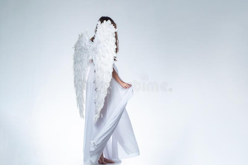 Angel girl. Long white wings. Wonderful blonde angel girl with white wings. stock photo