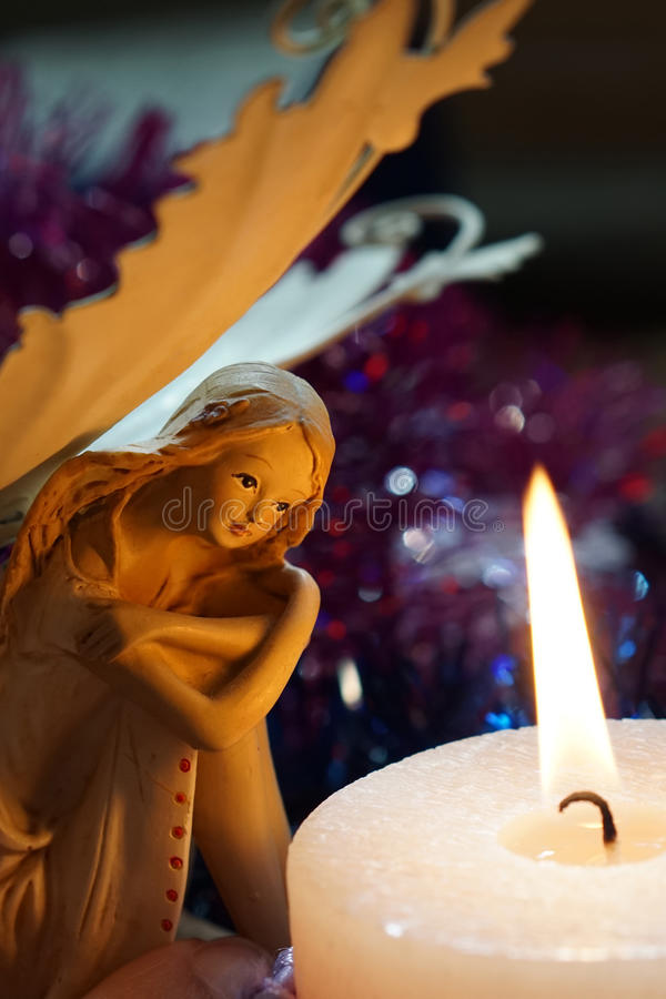 Angel is heated at a candle flame royalty free stock image
