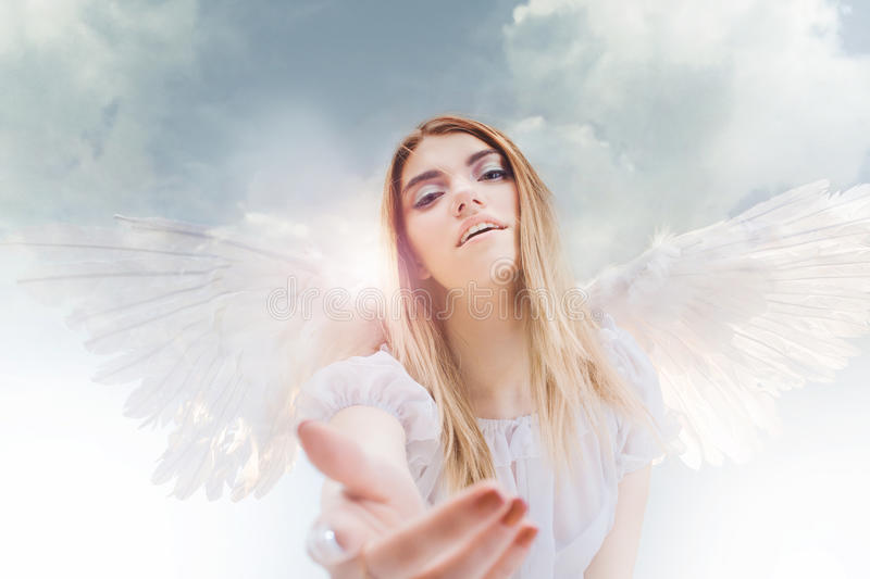 An angel from heaven gives you a hand. Young, wonderful blonde girl in the image of an angel with white wings. royalty free stock image