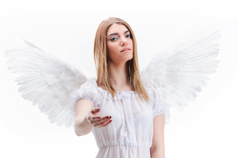 An angel from heaven gives you a hand. Young, wonderful blonde girl in the image of an angel with white wings. royalty free stock photo
