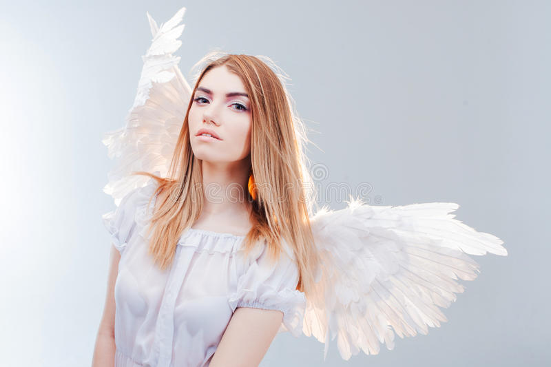 An angel from heaven. Young, wonderful blonde girl in the image of an angel with white wings. royalty free stock photos