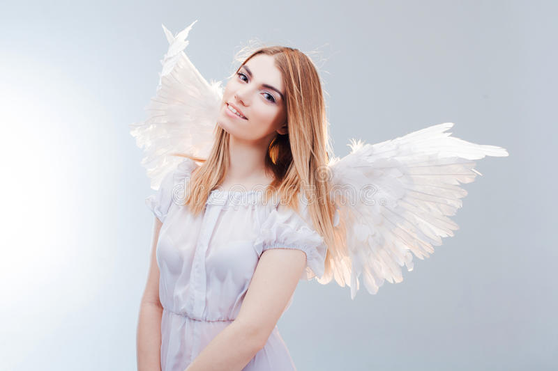 An angel from heaven. Young, wonderful blonde girl in the image of an angel with white wings. stock images