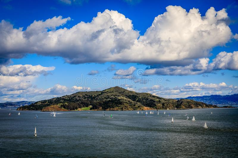 Angel Island with scattered sailboats and perfectly placed white clouds in a clear sunny day seen from Sausalito stock photos