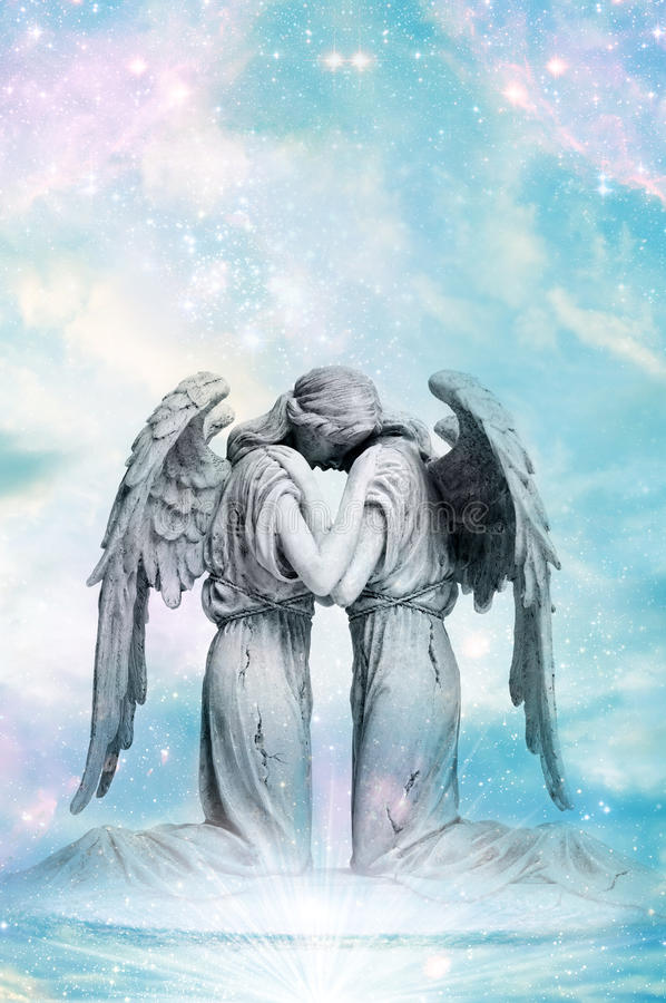 Angel love. A statue of embracing angels with rays of light like a concept for angel love stock images