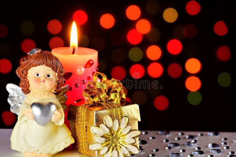 Angel of love Cupid, gift, pink candle and rainbow lights festive background with hearts and bright lights royalty free stock image