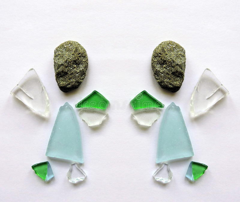 Angel made from glass and stone. Two angel made from glass and natural stone on white paper stock images