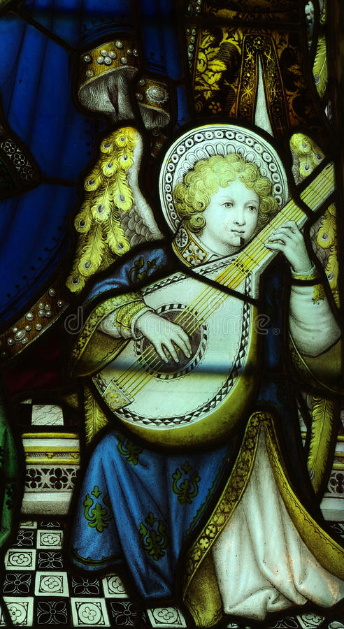 Angel making music in stained glass royalty free stock photo