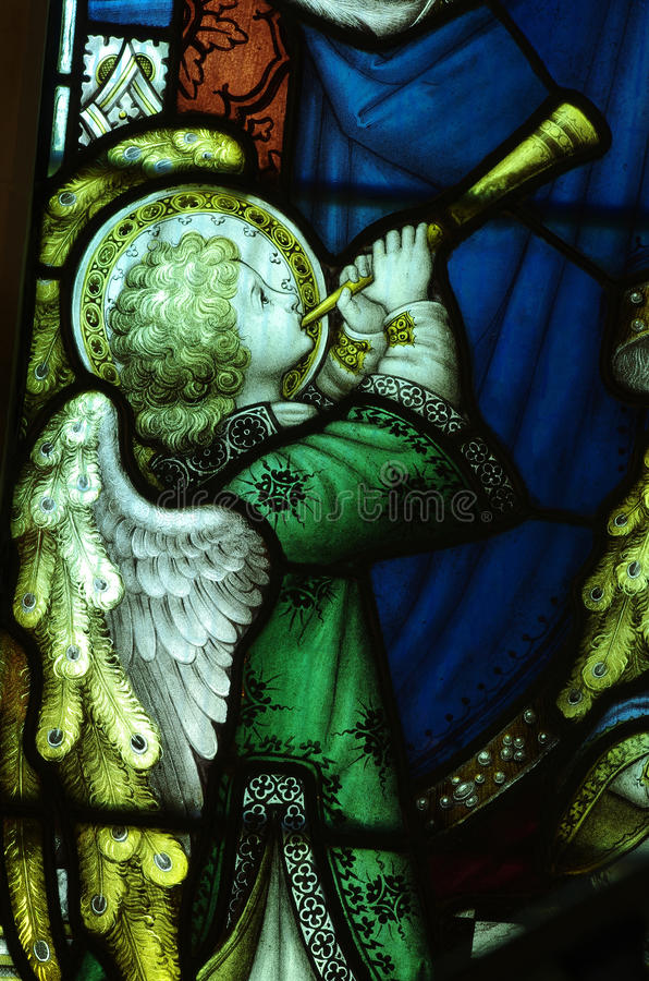 Angel making music with a trumpet (stained glass) stock images