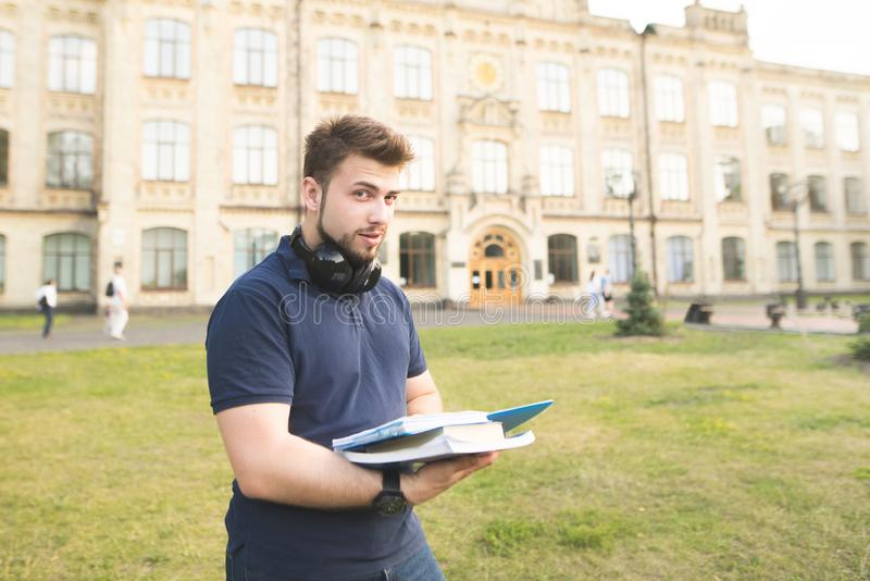An angel man stands in the street near the campus with books in his hands and looks at the camera. Portrait of a positive student on the background of the royalty free stock photos