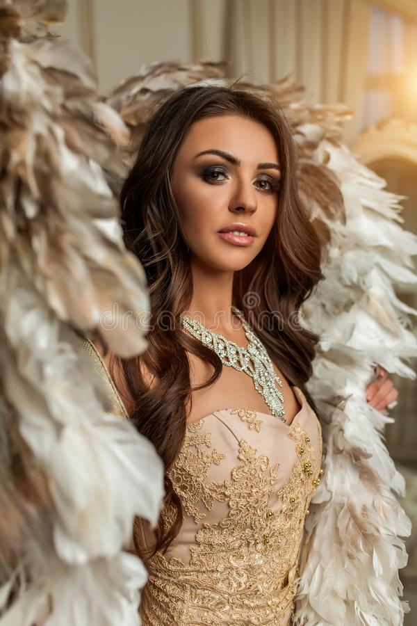 Beautiful brunette woman stands with gold and white wings in the stock photos