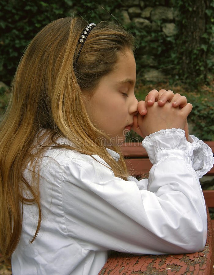 Angel in prayer 2. Angel (cute girl) in white dress, and closed eyes with his clasped hands folded in prayer. Vertical color photo