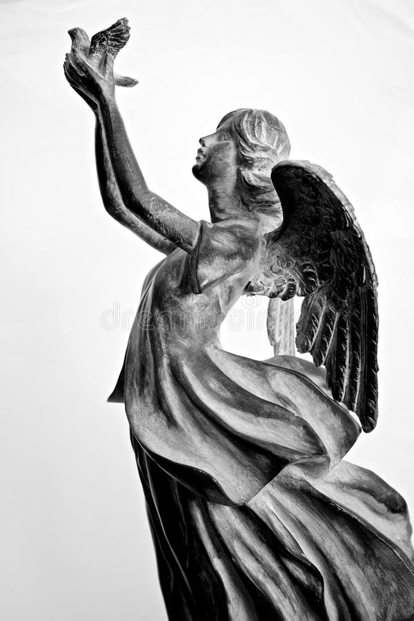 Angel releasing dove of peace. Angel statue in flowing gown sending off dove of hope, peace, and prosperity stock images