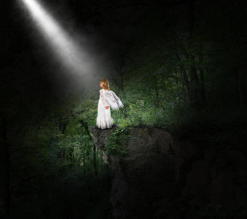 Angel, Religion, Heaven, God, Christian, Christianity. A young angel girl stands in a deep dark forest on a rock ledge with a beam of light shining from heaven stock image
