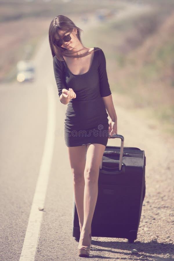 Angel. road suitcase instagram. Beautiful brunette woman black dress sunglasses, long hair elegant slim body, instagram filter style, shallow depth of field stock photo