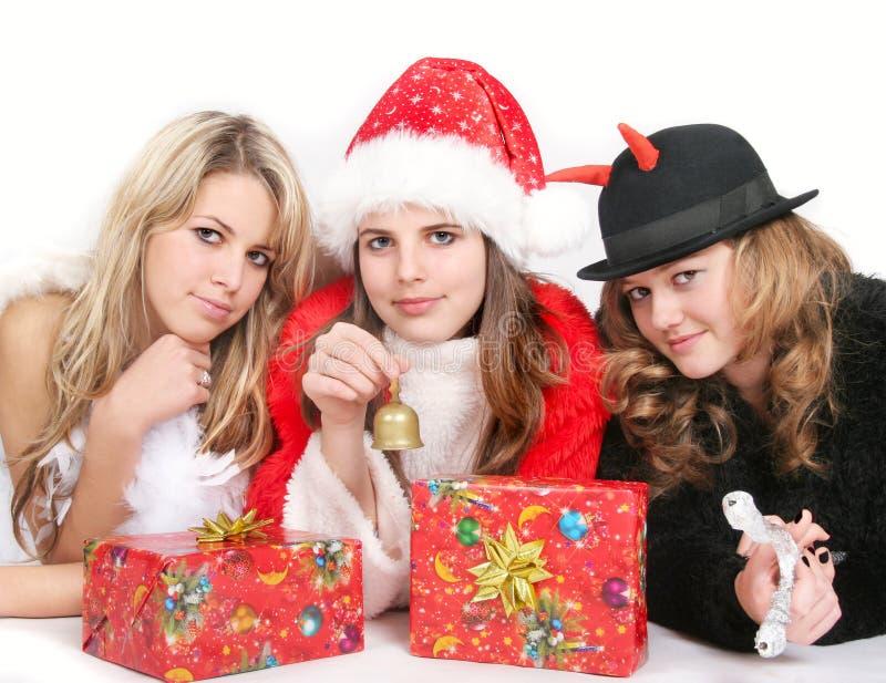Angel, Santa and tweedledum. Portrait of girls in red Santa´s, angel´s and tweedledum´ s costume stock image