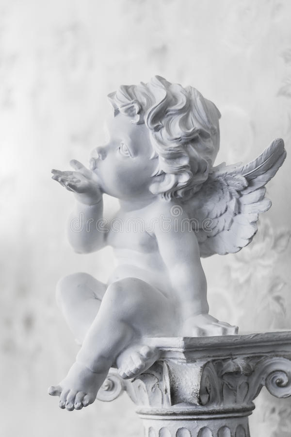 Angel sends an air kiss. Angel figurine symbolizing a child prodigy, love, family. It can be used as background for the congratulations on the newborn, wedding stock photo