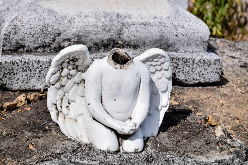 Angel statue without a head on a cemetery stock photography