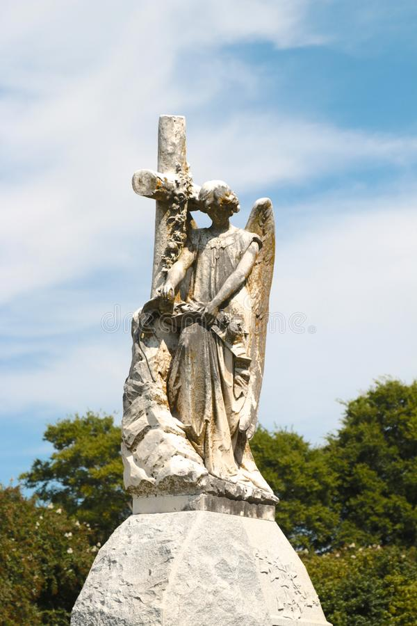 Angel Statue on a mound beside a Religious Cross. Female Angel Statue atop a mound with her head bowed beside a Cross stock photos