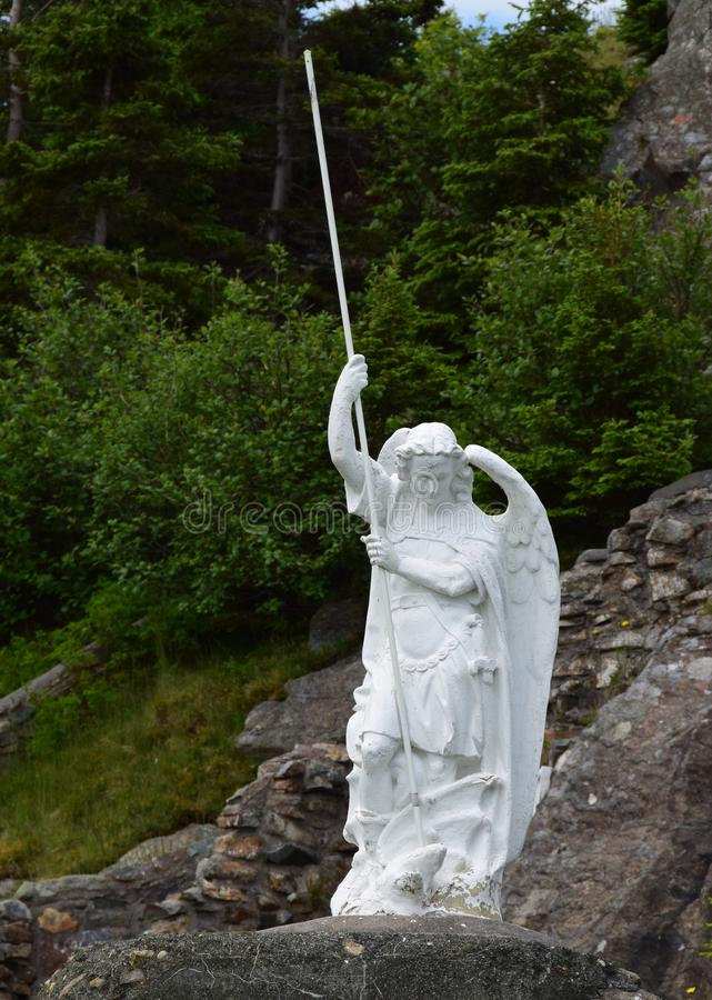 Angel statue with a spear. Closeup of an Angel statue with a spear, green forest area in the background stock photo
