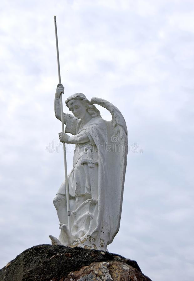 Angel statue with a spear. Looking up towards an Angel statue with a spear , cloudy sky in the background royalty free stock photography