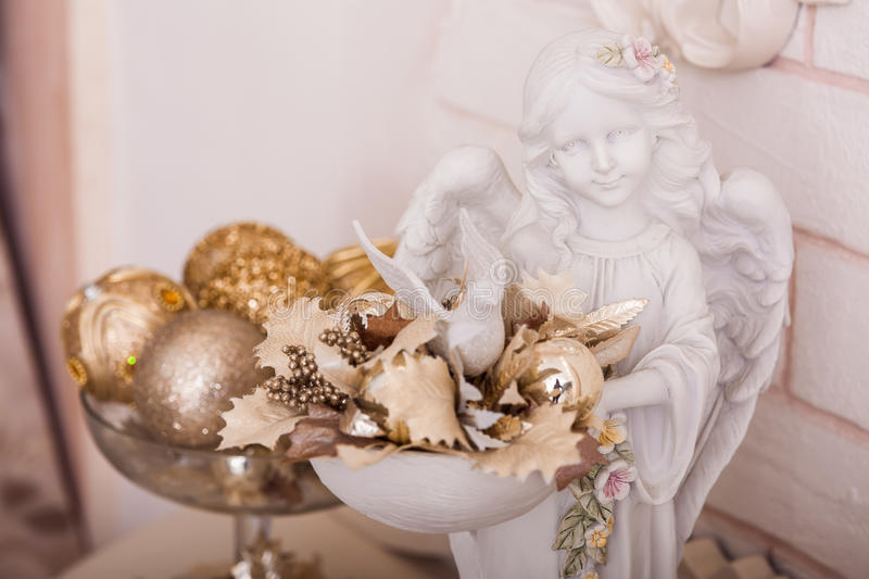 Angel statuette holding a bowl with golden Christmas ornaments. And leaves. Close-up stock photo