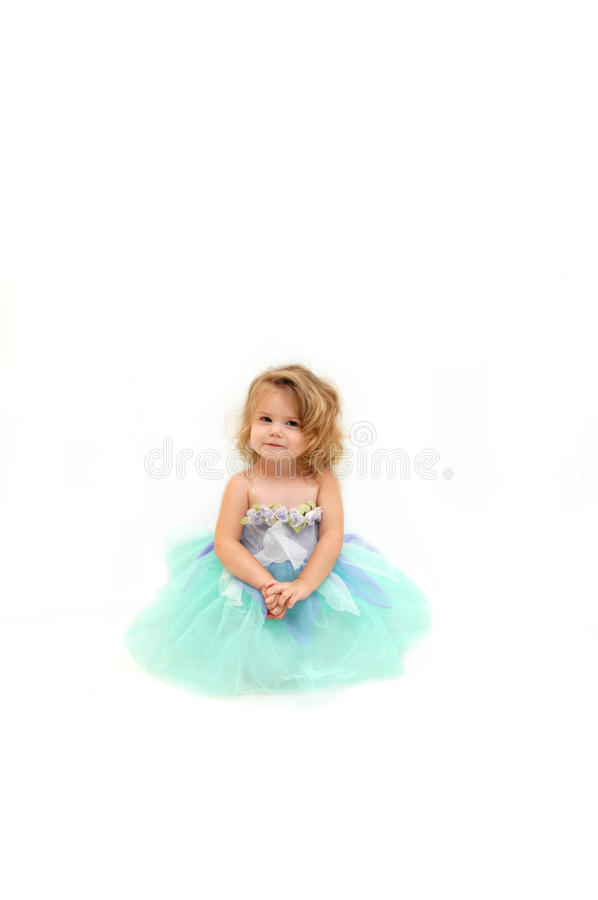 Angel in Tutu. Beautiful little girl wears a ballerina costume and sits in an all white room. She has blond curls falling around her face and is looking dreamy royalty free stock image