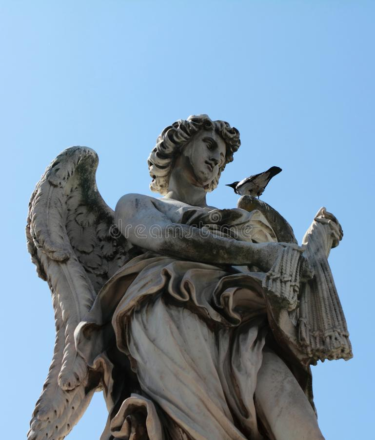 Angel with the Whips sculpture in Rome Italy with pigeon resting on his shoulder. royalty free stock image