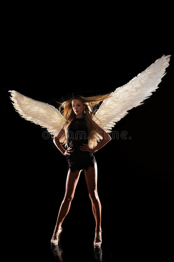 Angel with wings on black background stock photos