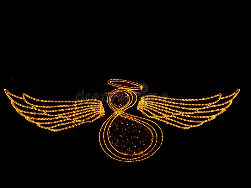 Angel with wings made of lights on black background royalty free stock images