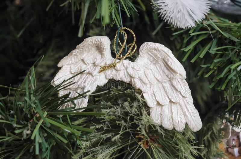 Angel wings ornament on a christmas tree. Close up of angel wings ornament hanging on a christmas tree royalty free stock photos
