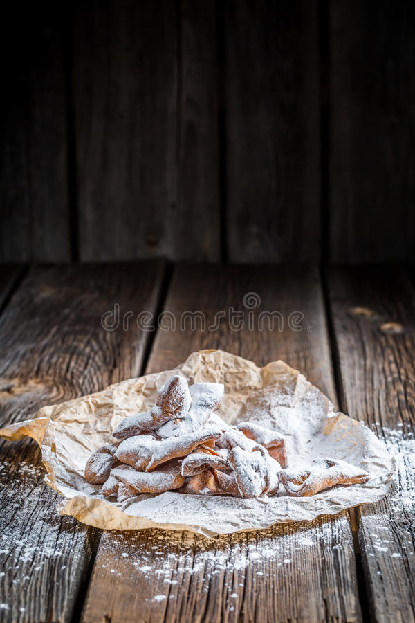 Angel wings with powdered sugar on baking paper. On old wooden table royalty free stock photo